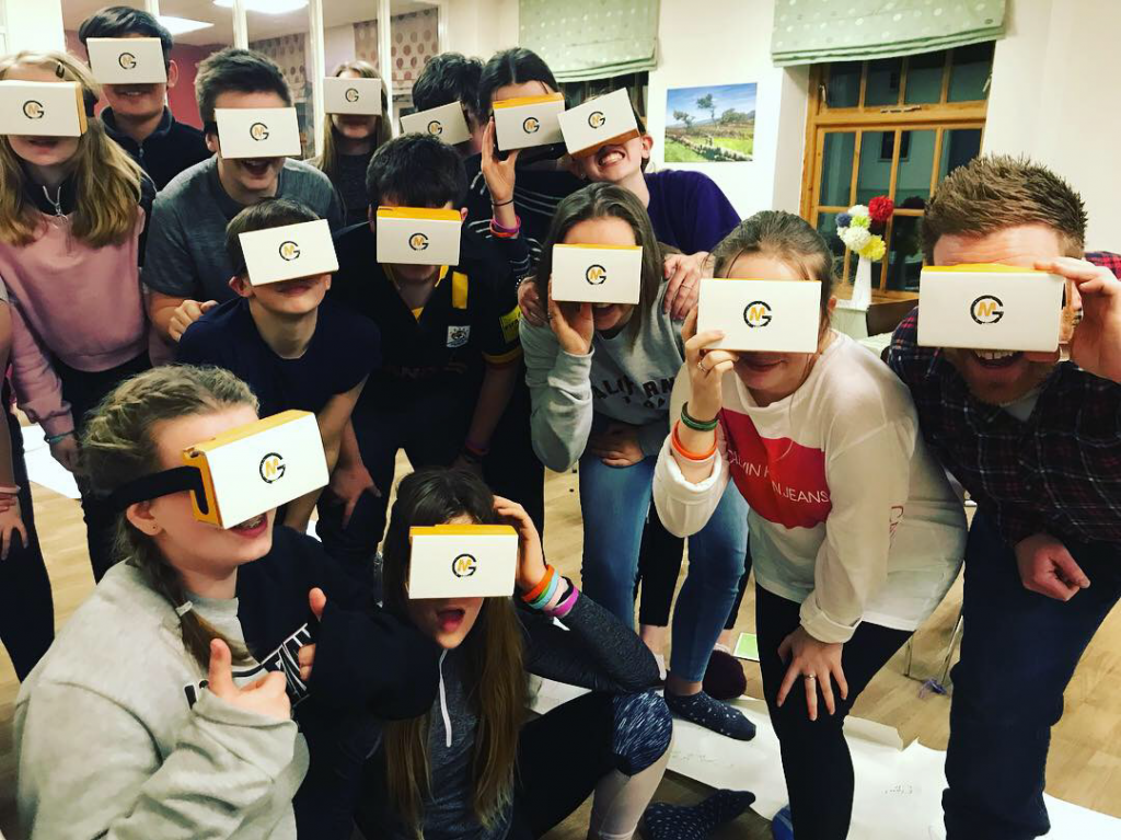 A youth group all wearing cardboard VR headsets